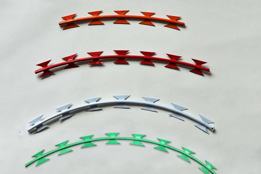 An orange, a red, a white and a green PVC coated concertina wire on the gray background.