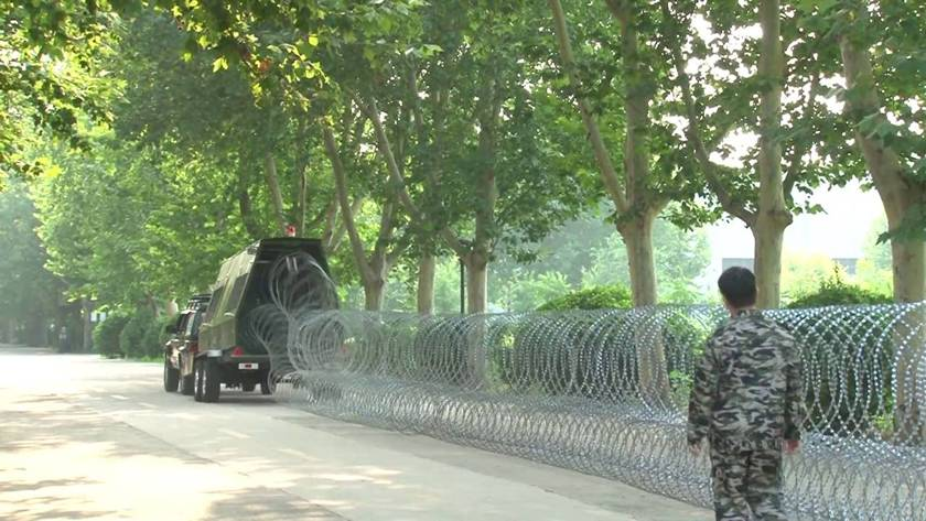 A trailer is placing the razor wire barriers in military site.