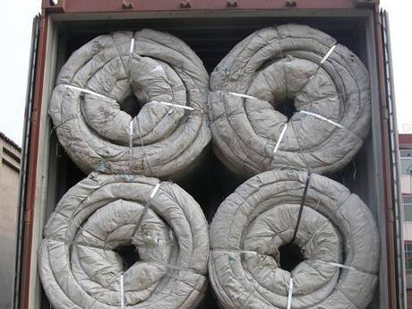 Concertina wire coils with woven bag package loaded in container for delivery.